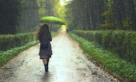 beautiful girl walking under rainfall in autumn park
